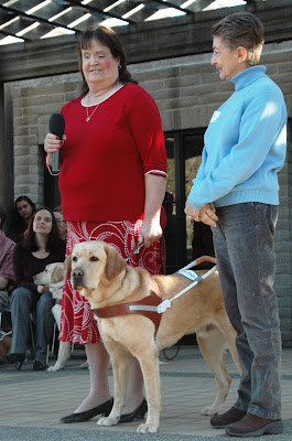 April with yellow Lab Epic and raiser Darleene on graduation stage