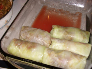 Stuffed cabbage rolls being loaded into roasting pan
