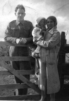 A man in army uniform leaning on a five barred gate, on this side separated from him by the gate is a woman wearing a head scarf and long over coat holding a small child