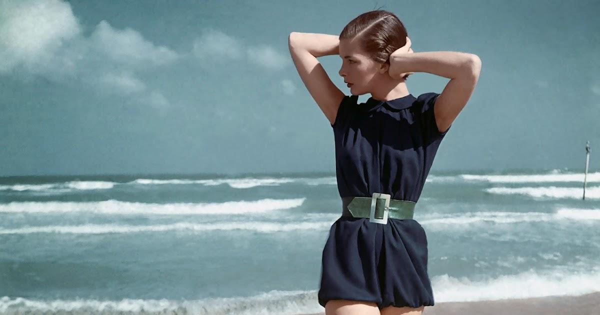 Model Walking On Beach Wearing A Blue Swimsuit By Caroline