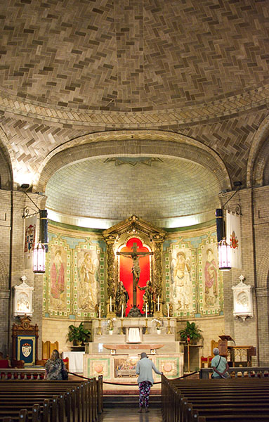 Red altar of St. Lawrence Basilica with lady paying reverence to the crucified Christ