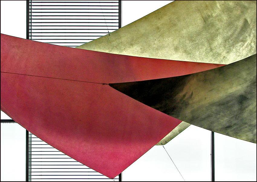 Conjunto de velas de tecido suspensas no ar com uma estrutura de barras paralelas horizontais por detrás