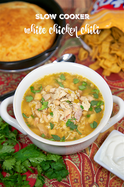 Slow Cooker White Chicken Chili recipe - chicken, seasonings, cannellini beans, chickpeas, green chilies - top with cilantro, cheese, sour cream and Fritos! SO good! Just dump everything in the slow cooker and forget it. Complete the meal with some cornbread. Quick and easy weeknight meal!