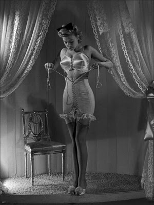 1940s lady in a bullet bra and boudoir slippers, lacing a vintage corset girdle