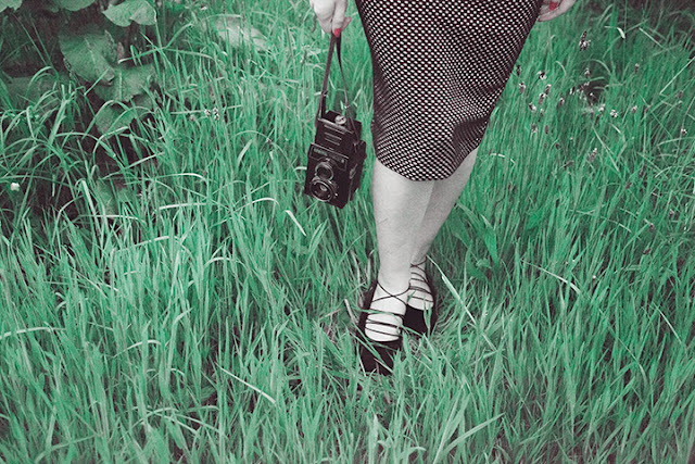 Low view of a woman's legs standing in grass wearing a pencil skirt with vintage camera