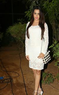 Actress Deeksha Panth Pictures in Short White Lace Dress at Bham Bolenath Audio Launch  77.jpg