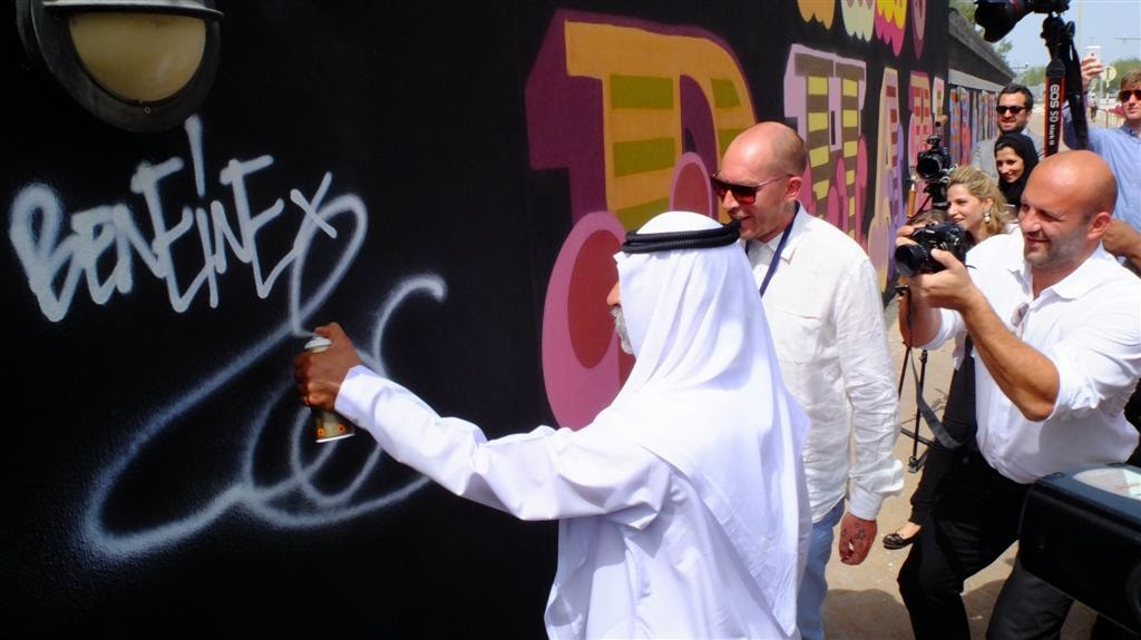 "Ahead of his debut solo in the Gulf region, British artist Ben Eine has just completed a 40-metre  outdoor mural  on the walls  of  the  British  Embassy  in  Abu  Dhabi. Working alongside students from Zayed University , the 40-meters Embassy mural reads: ""Beauty Is In The Eye Of The Beholder""; a comment on the juxtaposition of the traditional and the modern that encapsulates the dynamics of this unique region."