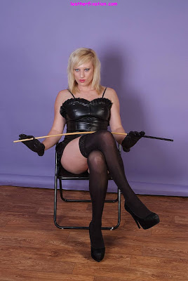 Leather Femdom Babe in Leather Dress and Stockings Posing with Cane