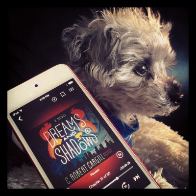 Murchie sits at attention, his ears perked and his focus on something to the right of the frame. He wears a blue shirt mostly obscured by a red-bordered iPod with the cover of Dreams and Shadows on its screen. The cover features the title in white against a dark blue background with flamelike red shapes around it. A city's silhouette is visible along the bottom.