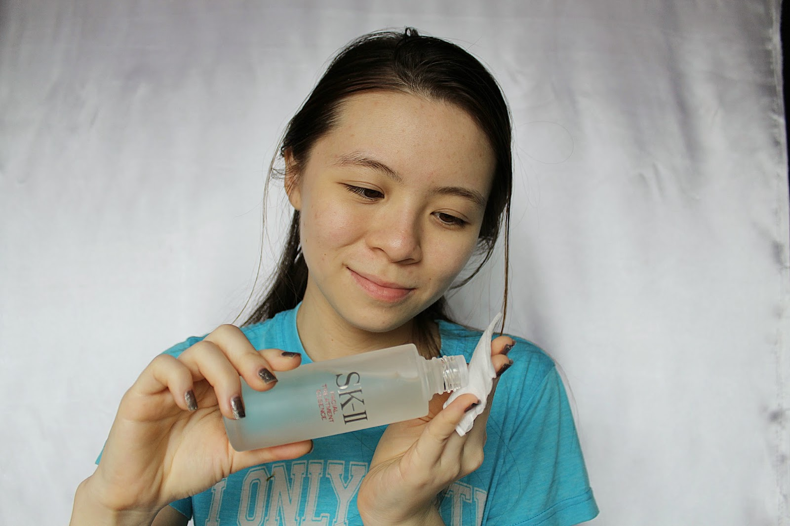 Girl pouring skincare on cotton pad
