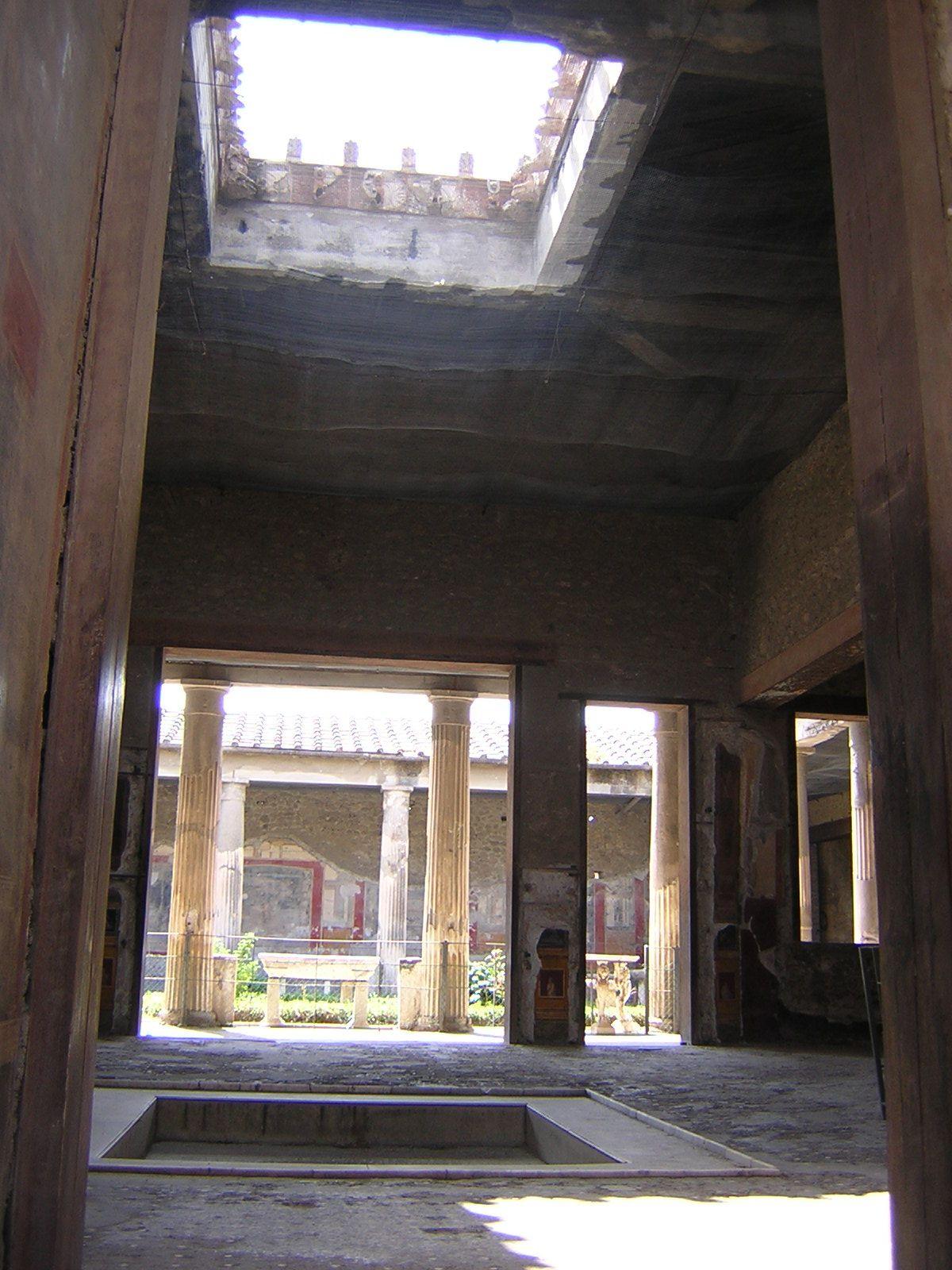 Casa de los Vetii. 3. Vista del atrio y el peristilo desde el vestíbulo. Compluvium atesonado e impluvium de mármol