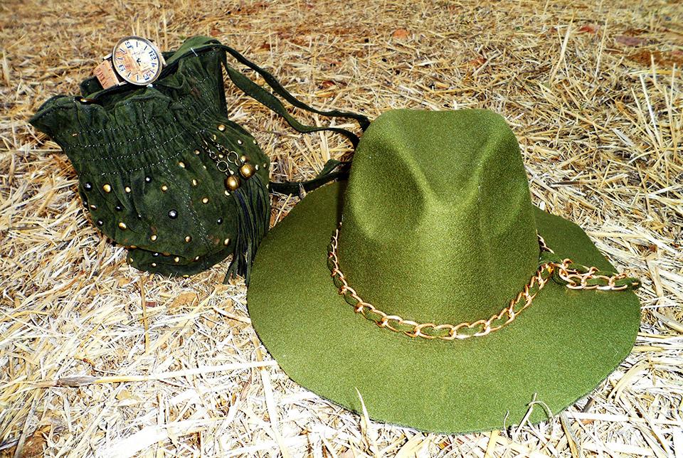 Bolso verde con tachuelas, sombrero verde con cadena y reloj marrón envejecido