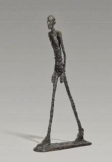Imagen de una escultura de Giacometti, realizada en bronce en 1960, que muestra a un hombre caminando.