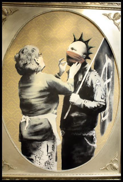 Untitled work by Banksy from his Bristol Museum Vs. Banksy show. The image depicts an anarchist, with a spiky mohawk, red scarf tied around his nose and mouth, and a black flag on a pole held against his shoulder. In front of him stands his mother, who is trying to straighten his red scarf before he goes out. Photograph by Josh Blair.