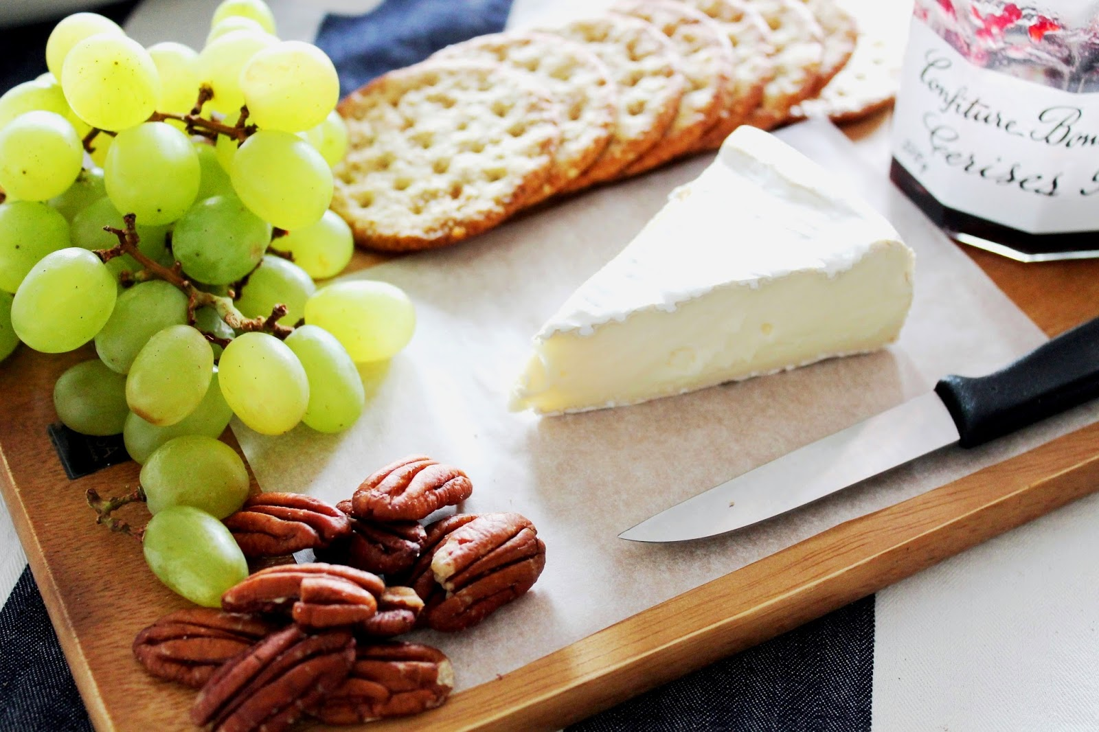 simple cheese plate anyone can afford with grapes, nuts, crackers, cherry jam and brie cheese