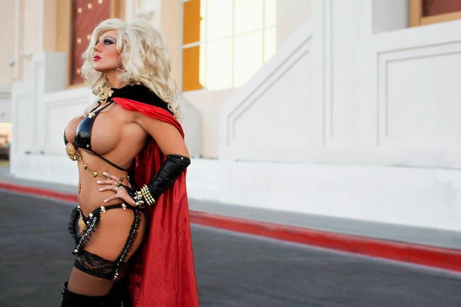 photo de cosplay de la wondercon 2014 d'une femme blonde en cape rouge et noire et forte poitrine siliconée