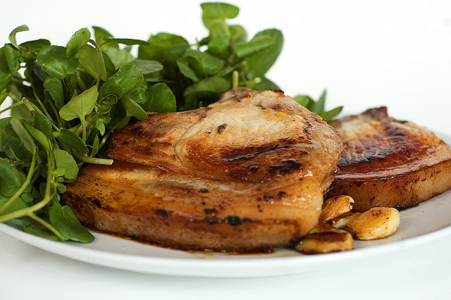 A dish of two pork chops and salad
