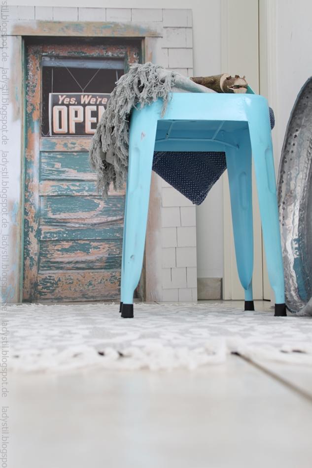 Blick auf den ganzen Flur mit türkisem Hocker, Accessoires und dem Tür-Poster