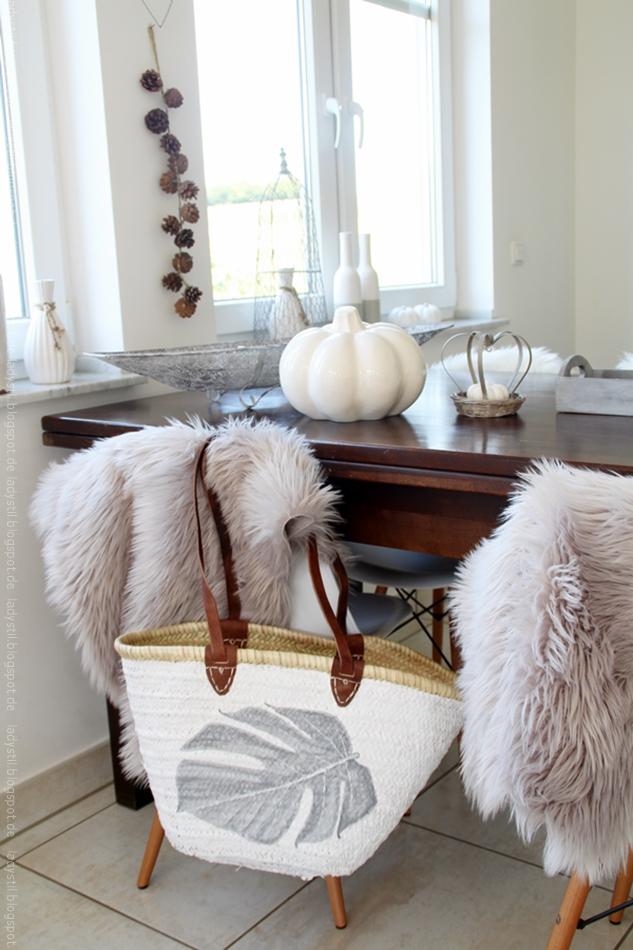 Korbtasche mit aufgemlatem grauen Monsterablatt hängt an einem Eameschair mit Fellüberwurf vor einem Tisch mit Kürbisdeko