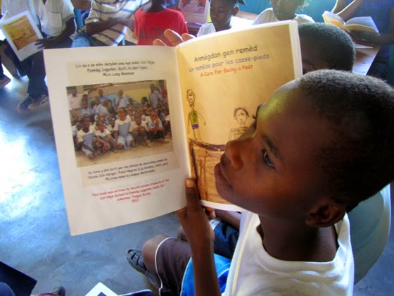 "Fifth-grader Kervenson Succès reads a student-authored book, ""A Cure for Being a Pest,"" printed in Creole, French and English. Credit: Amy Bracken (Used with permission)"