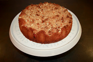 Rhubarb and marzipan crumble cake on a cake stand