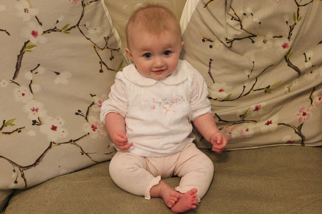 baby sat on sofa wearing pale pink leggings & white blouse with a flower pattern and peter pan collar from next