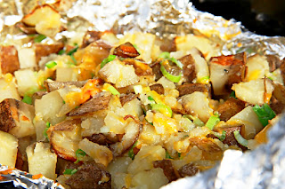 cooked potatoes that are diced with green onions in a foil pack