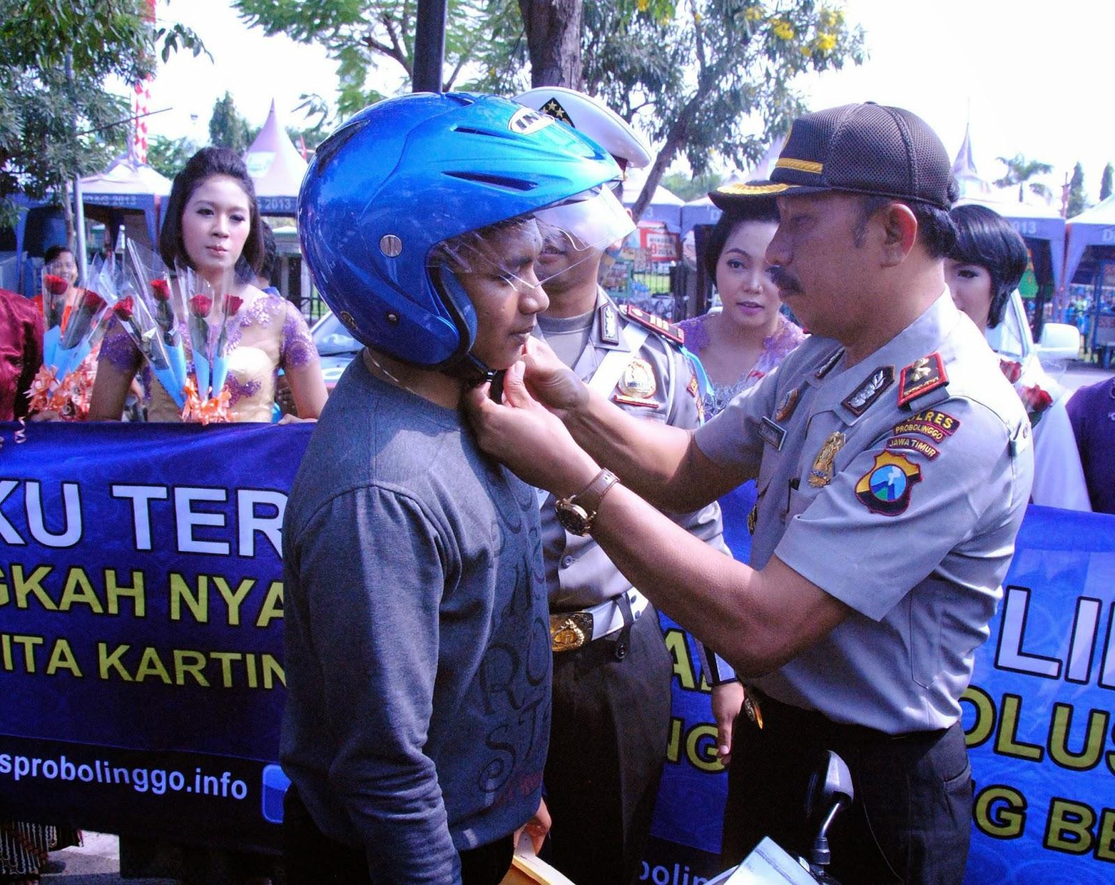 Wakapolres Probolinggo Kompol Sujiono, S.H. Memasangkan Helm Kepada Pengendara Motor