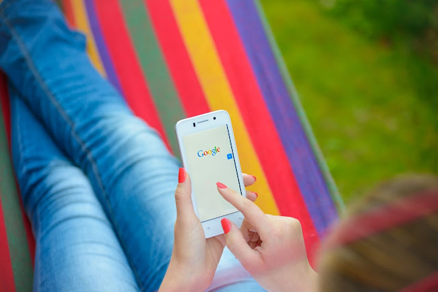 A woman lounges in a rainbow hammock and checks Google on her smartphone.