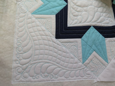 pretty feathered corner with double curved crosshatching done on a sewing machine and using quilting rulers