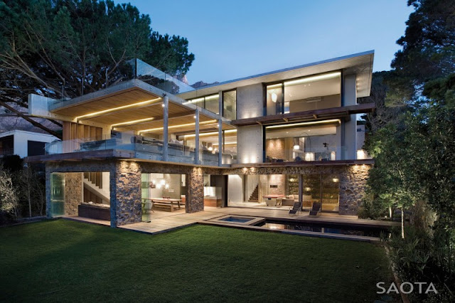 Photo of incredible modern home as seen at sunset from the lawn in the backyard