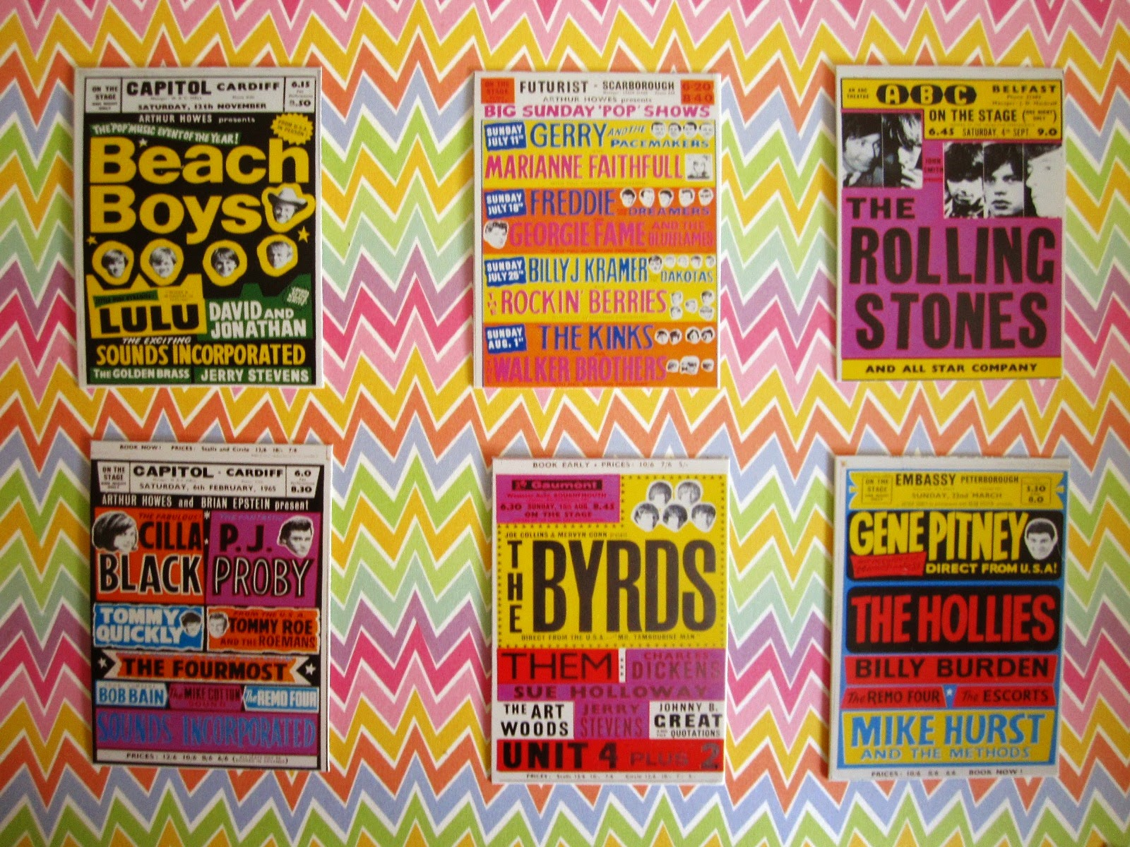 Selection of bright 1960s band posters arranged on a bright, zig zag-patterned wall.