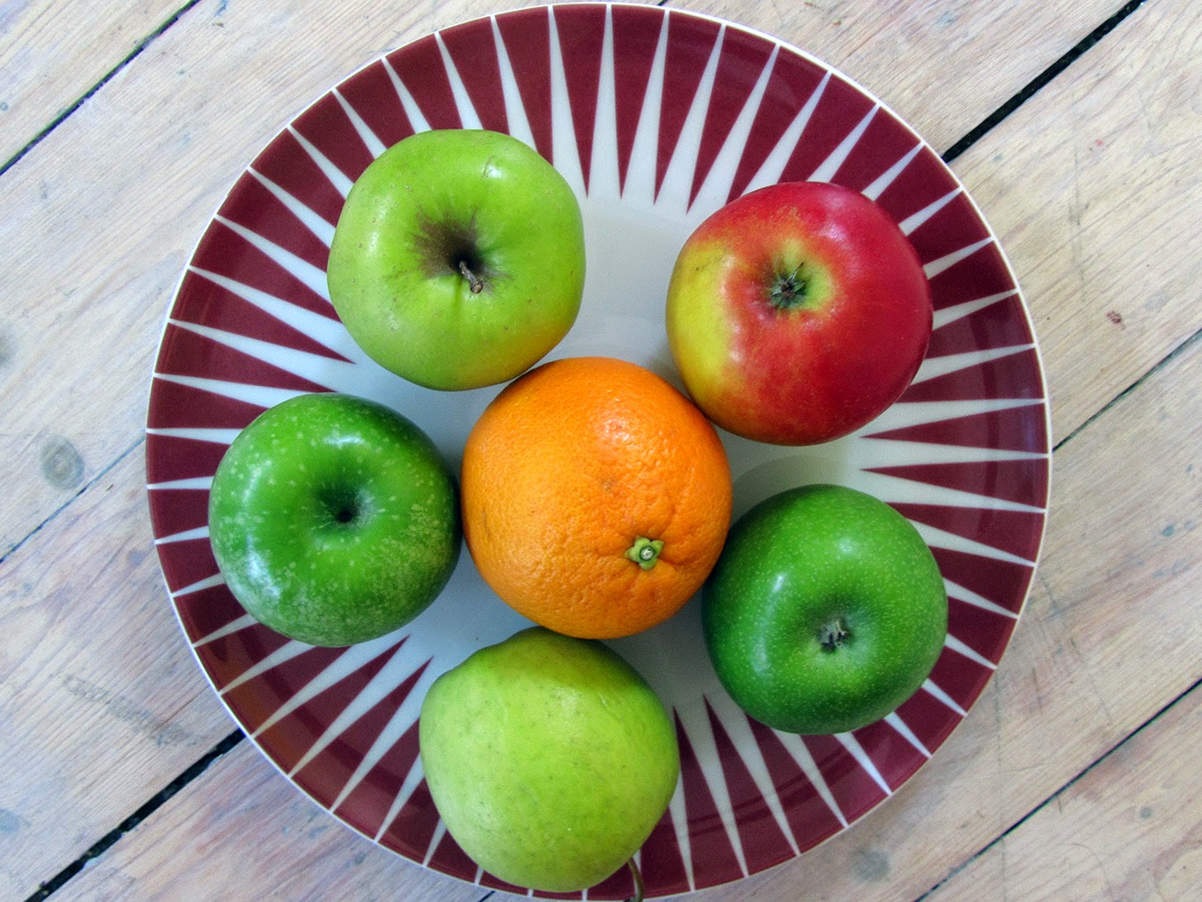 apples and an orange on an Ikea Bråkig plate