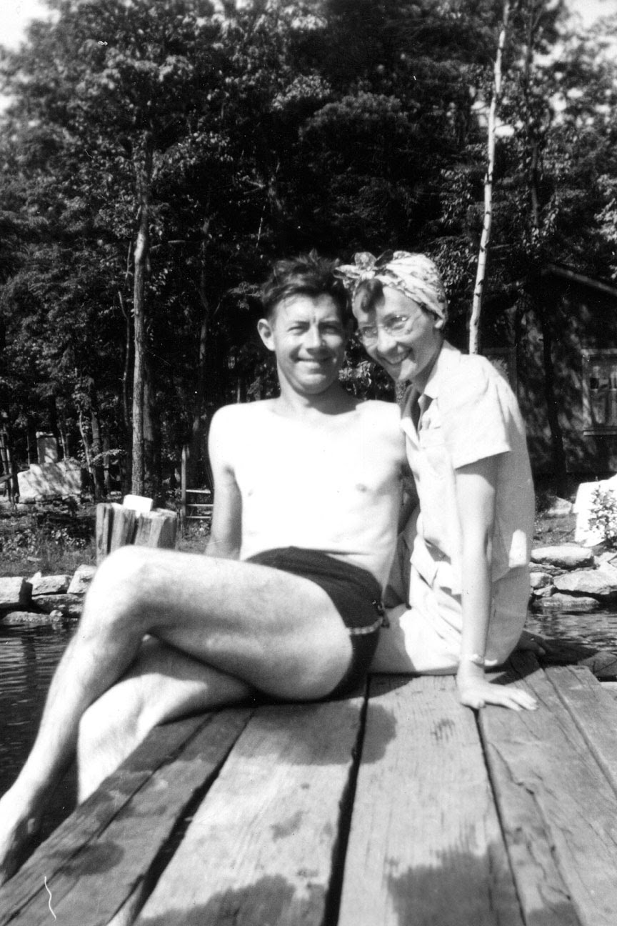 Poppa and Momma sitting on a dock by a lake