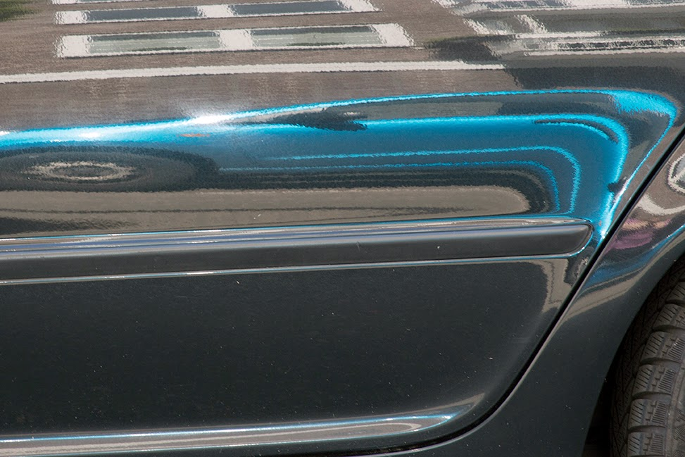 reflection of a blue car in a black car