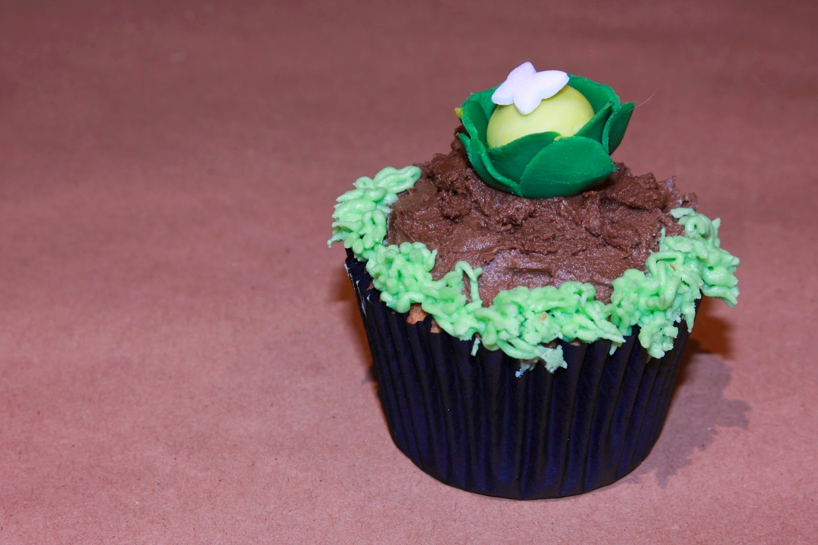 Earl Grey cupcake decorated with a caulliflower growing in a vegetable patch