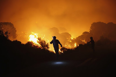 Brandweermannen houden de opmars van het vuur in de gaten in Cerro Alaminos de Sierra Negro bij Coín.