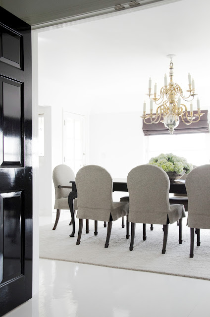 dinning room with black glossy doors, a gold chandelier, a dark wood table and gray chairs