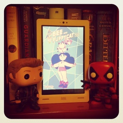 Tiny Hawkeye and Tiny Deadpool flank a white Kobo with Bee and Puppycat's cover on its screen. The cover features a plump, pale-skinned girl with large brown hair. A fat creature that looks rather like a Siamese cat perches atop her head. The background is shades of blue arranged in geometric shapes. Behind the Kobo, several hardcover books are visible, including Guardian of the Dead and Bitterblue
