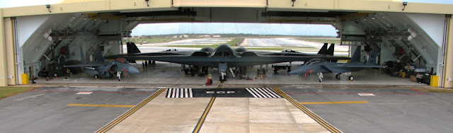 Two B-2 Spirit bombers and four F-15E Strike Eagles are parked inside Hangar 1 at Andersen Air Force Base, Guam.