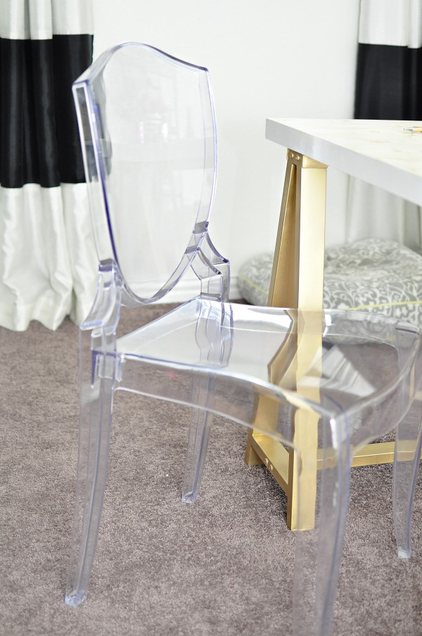 An acrylic ghost chair looks light and airy when paired with a black, white and gold color scheme for a home office.