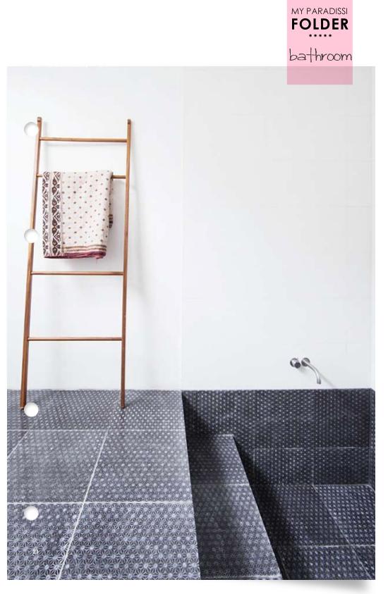 A bathroom with a recessed floor bathtub