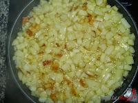 Tortilla española con queso y baicon-friendo papas y cebolla