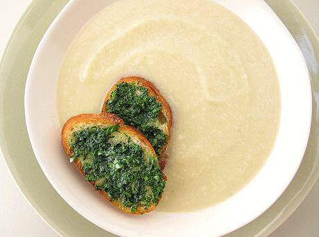 Romige knolseldersoep geserveerd met sneden Frans brood gegrild in de oven met olijfolie en fijngehakte peterselie en loof van de knolselder