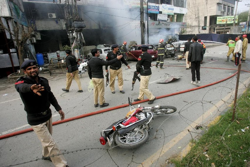 Pakistani police officers cordon off the site of a bombing in Lahore, Pakistan, Tuesday, Feb. 17, 2015. An apparent suicide bombing killed many people outside a police complex in eastern Pakistan on Tuesday, officials said, in a rare attack on the relatively peaceful city of Lahore.