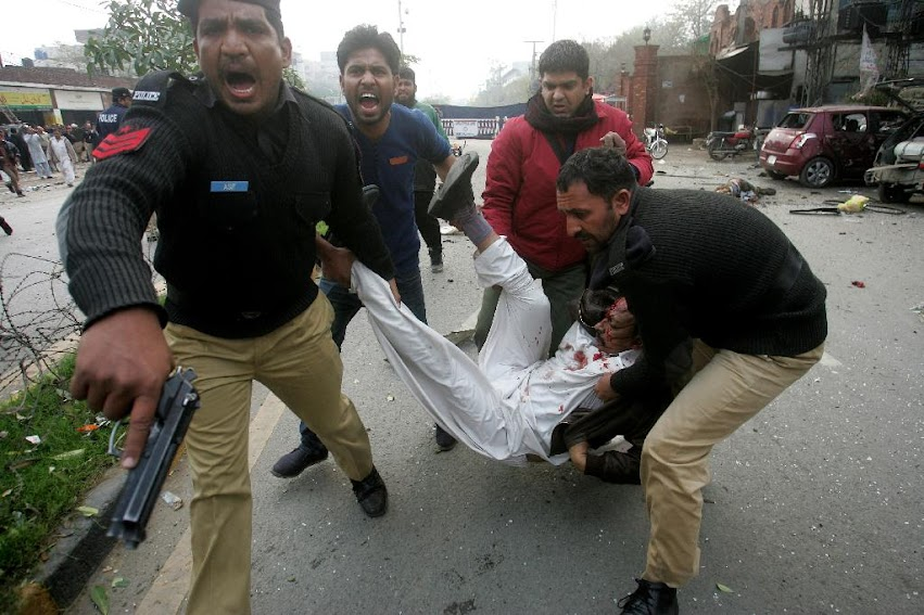 Pakistani police officers and volunteers rush an injured man to a hospital after a bombing in Lahore, Pakistan, Tuesday, Feb. 17, 2015. An apparent suicide bombing killed many people outside a police complex in eastern Pakistan on Tuesday, officials said, in a rare attack on the relatively peaceful city of Lahore.