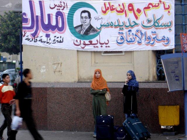 Niñas jovenes bajo  pancarta de Hosni  Mubarak.