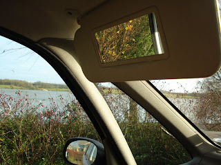 A view out of the passenger door with different reflection in the wing mirror and passenger visor