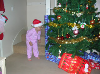 Top Ender leaning into the Christmas Tree looking at the gifts expectantly