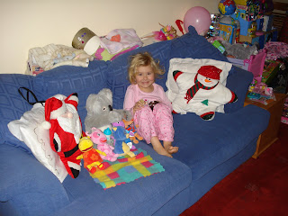 Top Ender sitting on the sofa with Toys and Christmas pillows watching a Christmas film
